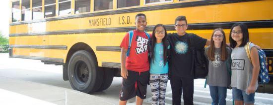 Kids standing in front of MISD school bus