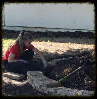 Volunteer Working on Flowerbed at Phoenix Academy