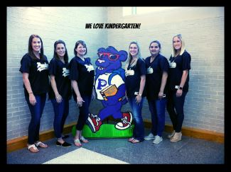 Six teachers smiling standing around a cutout purple panther