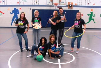 Enrichment teachers with tools of their trade-instrument, hula hoop, book, Ipad
