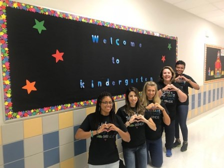 Kinder teachers standing in front of a bulletin board that says Welcome