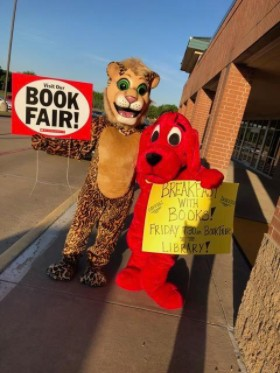 Jazzy the Jaguar and Clifford the Big Red Dog hold signs advertising the Tipps Book Fair